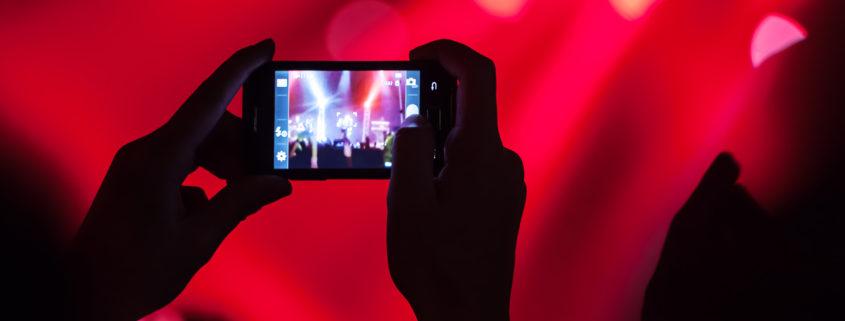 Smartphone vor rotem Eventhintergrund